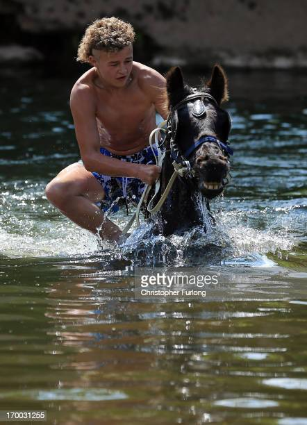 A traveller washes his horse in the waters of the River Eden in preparation for selling at the Appleby Horse Fair on June 6 2013 in Appleby England...