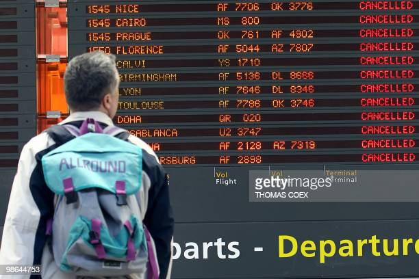 A traveller watches a board announcing cancelled flights on April 17 at the Roissy Charles de Gaulle airport near Paris Three airports in Paris and...