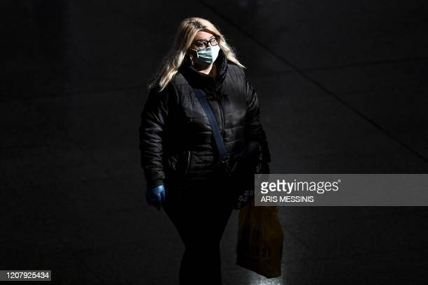 A traveller wearing a facemask for protective reasons walks in the departure hall at the Athens international airport on March 21 2020 As part of the...