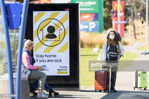 Traveller wearing a protective mask is seen waiting for a bus near Christchurch International Airport on March 18, 2020 in Christchurch, New Zealand....