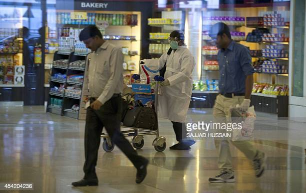 A traveller who was not cleared after being screened for the Ebola virus on his arrival in India walks towards an ambulance at the International...