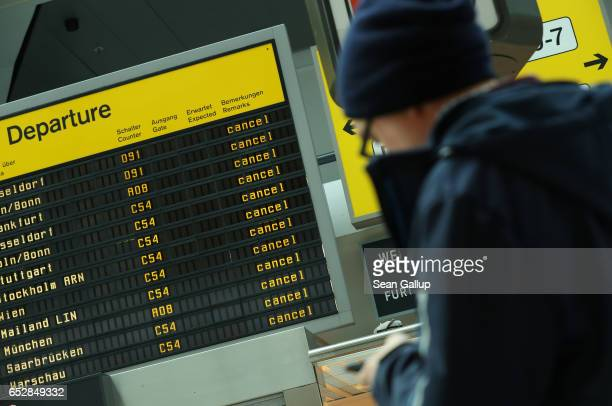 A traveller whose flight to Moscow was cancelled checks his mobile phone under a departures board that shows cancelled flights during a strike by...