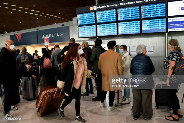 Traveller with a protective face mask pass by other standing in front of screens displaying departures flights at Paris-Charles-de-Gaulle airport...