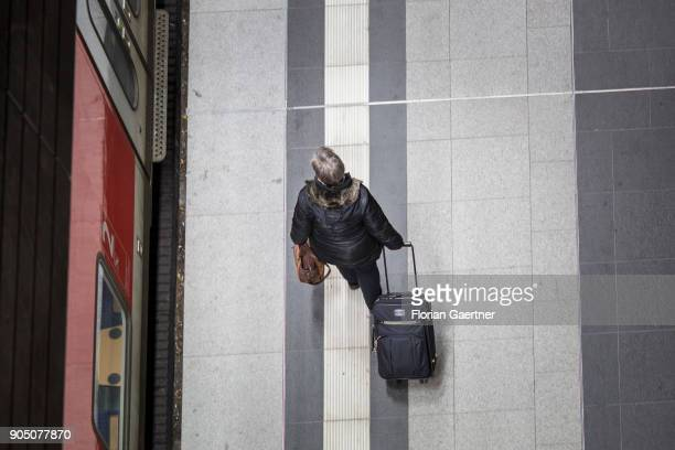 Traveller with trolley bag walks along a train on January 11, 2018 in Berlin, Germany.