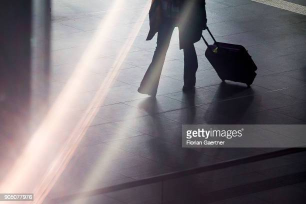 A traveller with trolley bag walks at the main train station on January 11 2018 in Berlin Germany