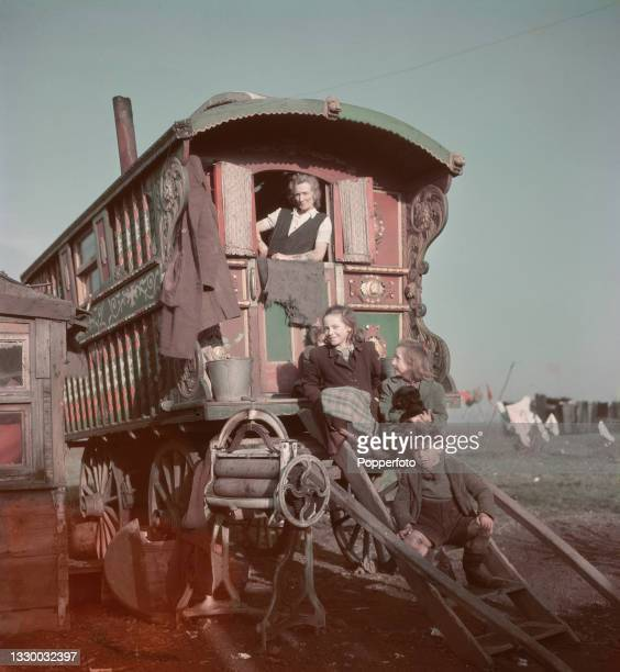 Traveller woman and three children stand in and sit on steps leading up to a traditional Romani horse drawn wagon, known as a caravan or Vardo, at a...