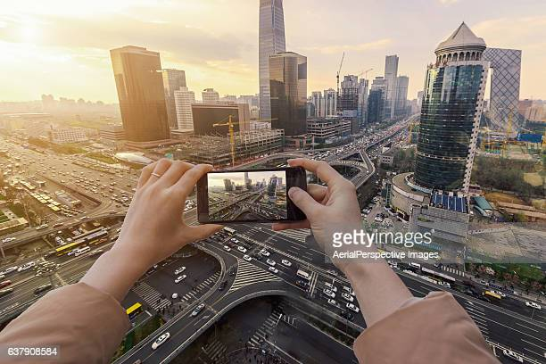 Traveller woman taking pictures with smartphone from personal point of view of the Beijing CBD at Sunset