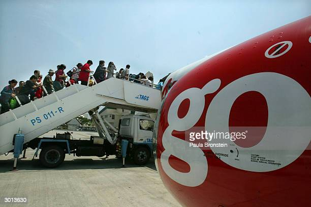Travellers are seen boarding the Air Asia Boeing 737300 flight from Bangkok to Phuket on February 25 2004 in Phuket Thailand The airline is the first...