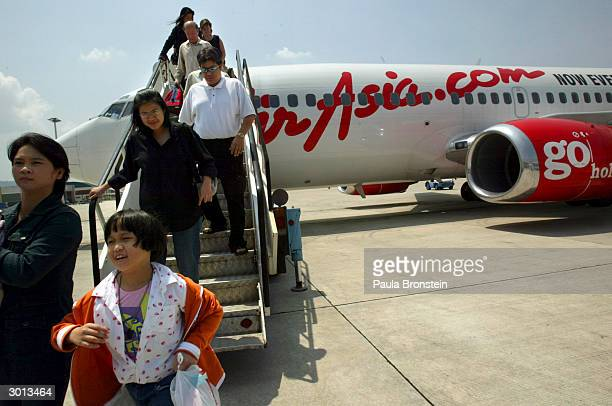 Travellers are seen disembarking from the Air Asia Boeing 737300 flight from Bangkok to Phuket on February 25 2004 in Phuket Thailand The airline is...