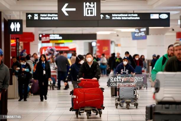 Travellers are seen wearing masks at the international arrivals area at the Toronto Pearson Airport in Toronto Canada January 26 2020 Toronto Public...