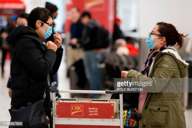 Travellers are seen wearing masks at the international arrivals area at the Toronto Pearson Airport in Toronto, Canada, January 26, 2020. - Toronto...