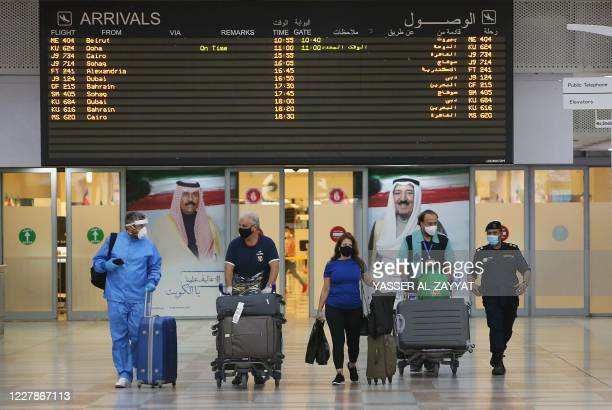 Travellers arrive at Kuwait international Airport, in Farwaniya, about 15kms south of Kuwait City, on August 1, 2020. - Commercial flights resumed at...
