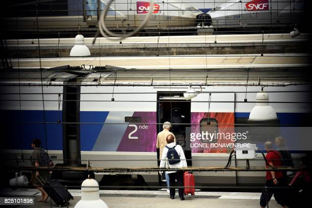 Travellers arrive to get on a train at Montparnasse train station in Paris on August 1 days after traffic was interrupted due to technical reasons...