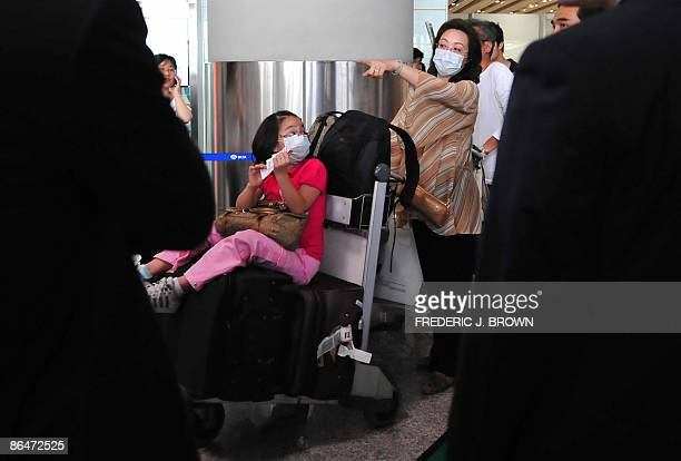 Travellers arrive wearing protective facemasks Beijing airport on May 7 2009 as China started lifting a sevenday quarantine on passengers who had...