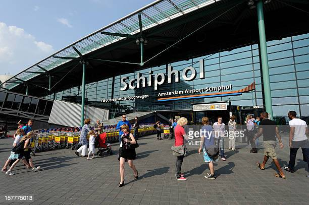 travellers at the entrance of amsterdam airport schiphol - schiphol airport stock photos and pictures