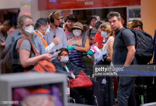 Travellers await for their flights out of Peru on March 16, 2020 at the Jorge Chavez international airport in Callao, Lima, minutes before borders...