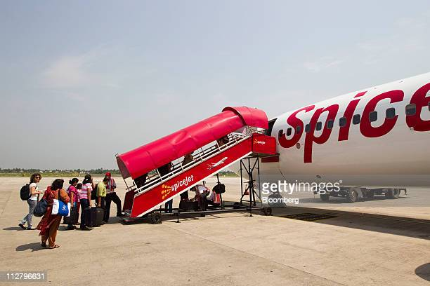 Travellers board a SpiceJet Ltd flight at Netaji Subhash Chandra Bose Domestic Airport in Kolkata India on Friday April 8 2011 Travel is surging in...