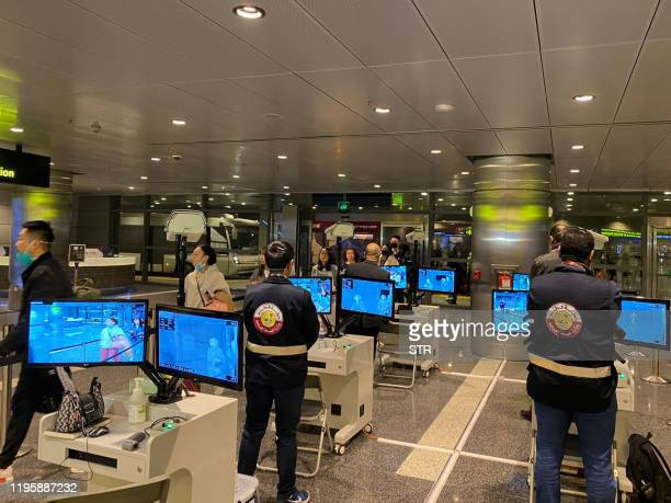 Travellers coming from Asia walk past scanners for temperature screening upon their arrival at Doha International airport in the Qatari capital on...