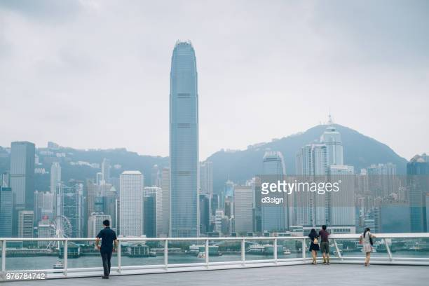 Travellers enjoying the spectacular city view and Victoria Harbour over the public area