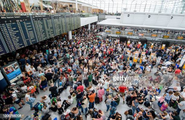 Travellers gather in front of information boards at the Terminal 2 at Munich airport on July 28 2018 as around 200 flights had to be cancelled and...