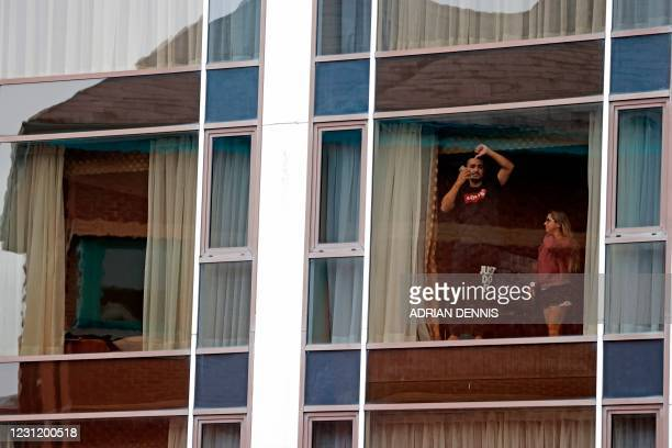 Travellers gestures as they look out of a window during mandatory hotel quarantine in a Radisson Blu hotel at Heathrow Airport in west London on...