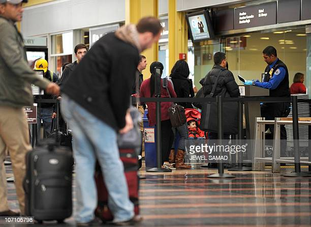 Travellers go through a Transportation Security Administration check point at the Regan National Airport in Washington DC on November 24 2010 ahead...