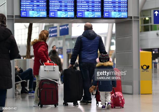 Travellers look at boards displaying information on flights at the airport in Duesseldorf western Germany on January 18 as wide parts of the country...