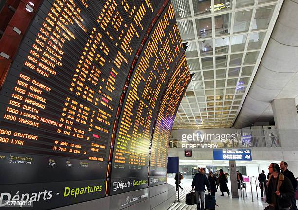 Travellers look at the departure board on December 22 2010 at the Charles de Gaulle airport in Roissy as 25% of the flights have been cancelled...