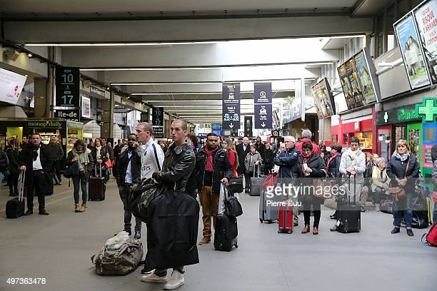 Travellers observe a minute's silence in memory of the victims of the Paris attacks after a Minute's silence at Montparnasse train station on...