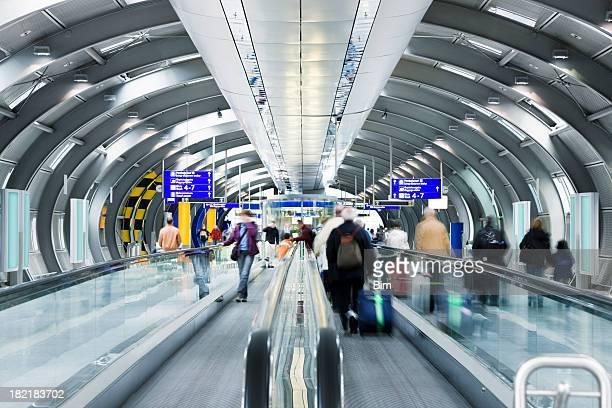 Reisende auf Fahrsteig im Flughafen