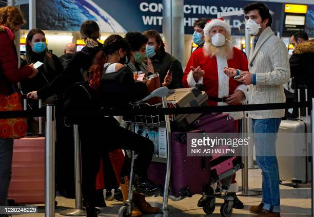 Travellers, one dressed in a Father Christmas outfit and all wearing face coverings, queue with their luggage in the departures hall at Terminal 2 of...