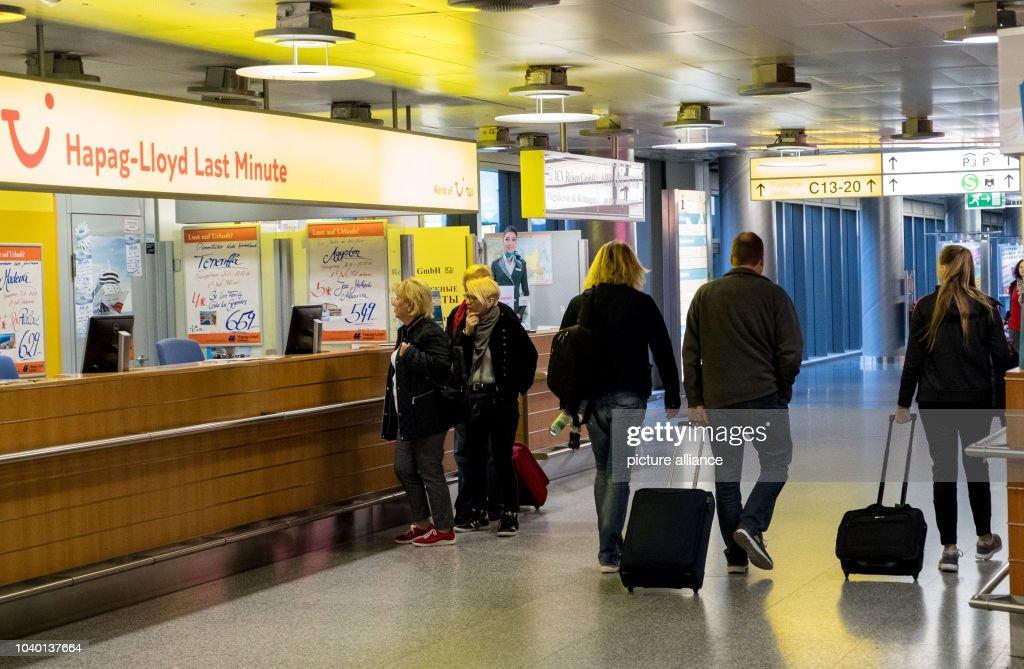 Travellers Pass The Counter Of A Travel Agents Featuring Tui Logo At Airport