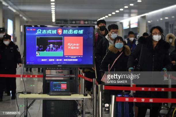 Travellers pass through a fever detection system developed by Chinese search engine Baidu at the Qinghe railway station in Beijing on February 6 as...