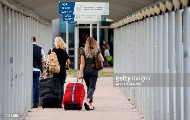 Travellers pull their suitcases as they arrive at London Stansted Airport, northeast of London on August 20, 2020 following the decision by British...