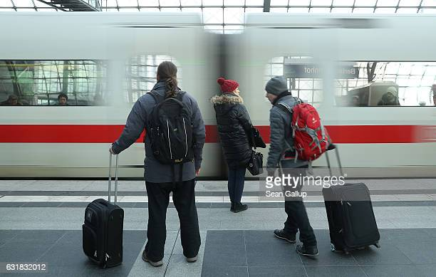 Travellers pulling suitcases prepare to board an arriving ICE highspeed train of German state rail carrier Deutsche Bahn at Hauptbahnhof main railway...