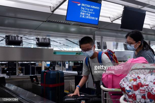 Travellers put their bags on the conveyor belt as they check in at Hong Kong's International Airport on July 18 the day before a deadline by the...