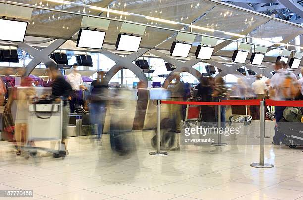 Travellers queing to check-in at an International Airport.