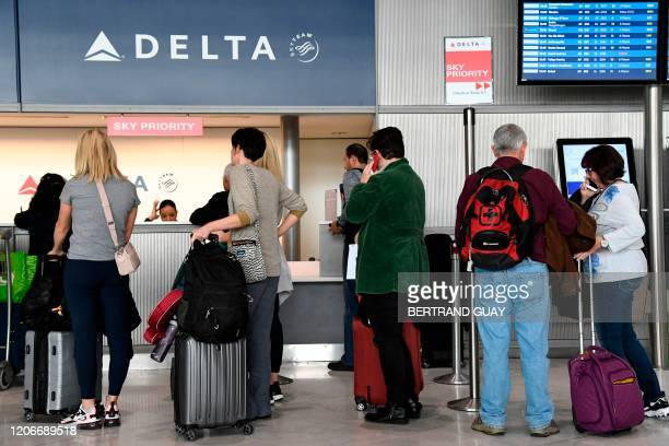 Travellers queue at a Delta Airlines desk at Paris-Charles-de-Gaulle airport after a US 30-day ban on travel from Europe due to the COVID-19 spread...