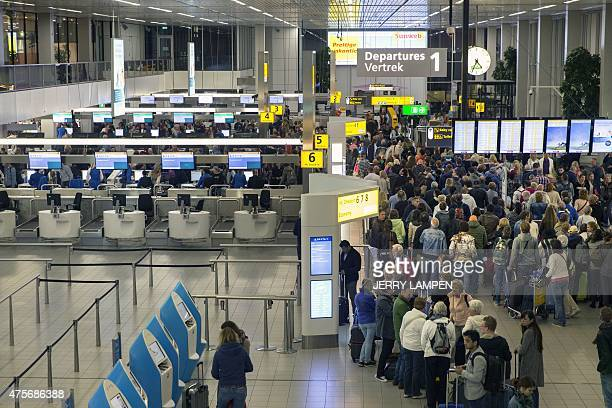 Travellers queue on June 3 2015 at the departure zone of the Amsterdam Airport Schiphol which has switched to central security for the entire airport...