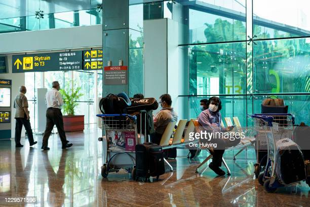Travellers sit and wait for their flight at the departure hall of Changi Airport Terminal 1 on November 11, 2020 in Singapore. Singapore and Hong...