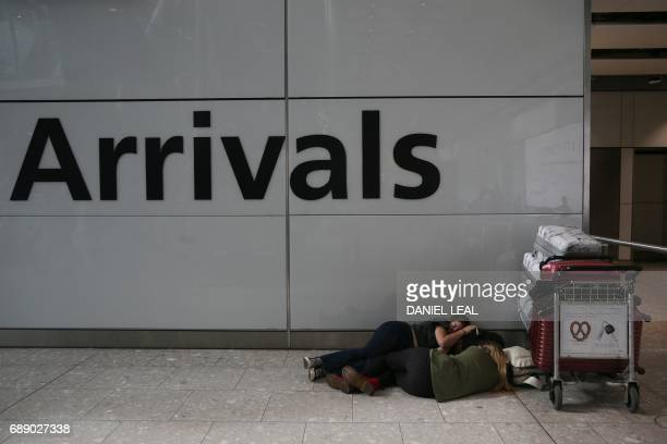 Travellers sleep next to luggage at Heathrow Airport Terminal 5 after British Airways flights where cancelled at Heathrow Airport in west London on...