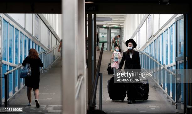 Travellers, some wearing a face mask or covering due to the COVID-19 pandemic, pull their suitcases as they arrive at London Stansted Airport,...