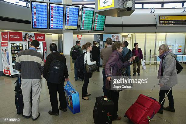Travellers stand in front of a departures board that shows cancelled Lufthansa flights at Tegel Airport during a nationwide strike by Lufthansa...