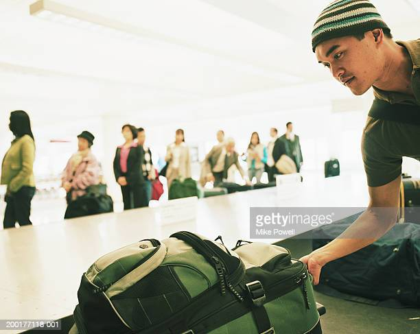 Travellers standing by airport carousel, young man picking luggage