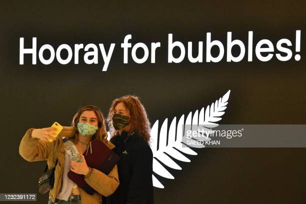 Travellers take selfies before their departure for New Zealand at Sydney International Airport on April 19 as Australia and New Zealand opened a...