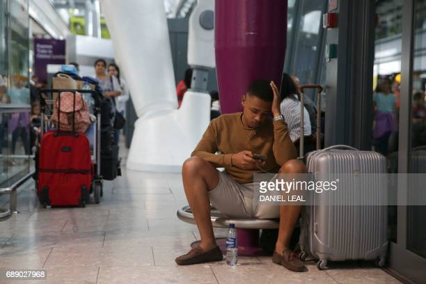 Travellers wait at Heathrow Airport Terminal 5 after British Airways flights where cancelled at Heathrow Airport in west London on May 27 2017...