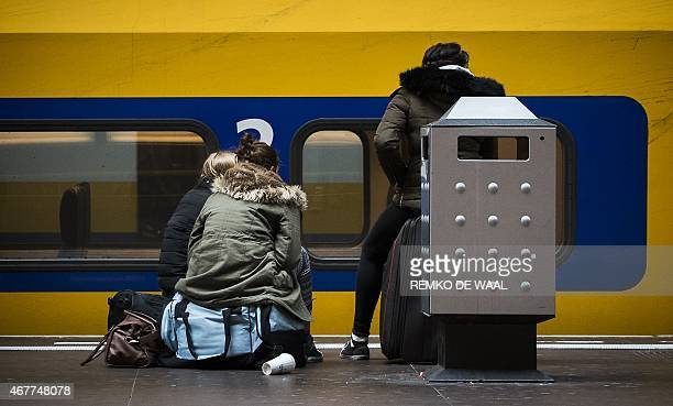 Travellers wait at the Central Station of Amsterdam on March 27 2015 during a major power outage Large parts of North Holland including neighborhoods...