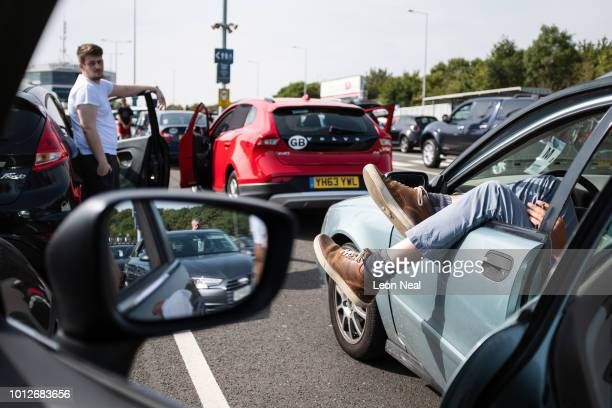Travellers wait by their cars as a delay continues for those heading out of England via the Channel Tunnel on August 7, 2018 in Folkestone, England....