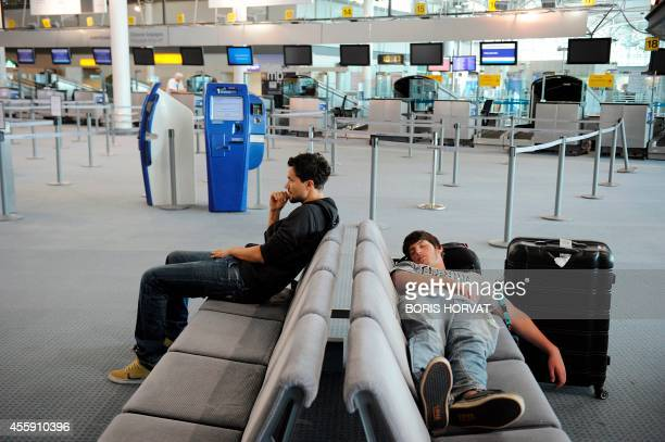Travellers wait for a flight at the MarseilleProvence airport on September 22 2014 in Marignane Air France has suspended until December its plans to...