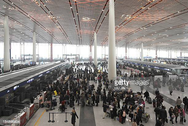 Travellers wait for flights at Beijing International Airport on December 5 2011 Beijing authorities cancelled hundreds of flights and shut highways...